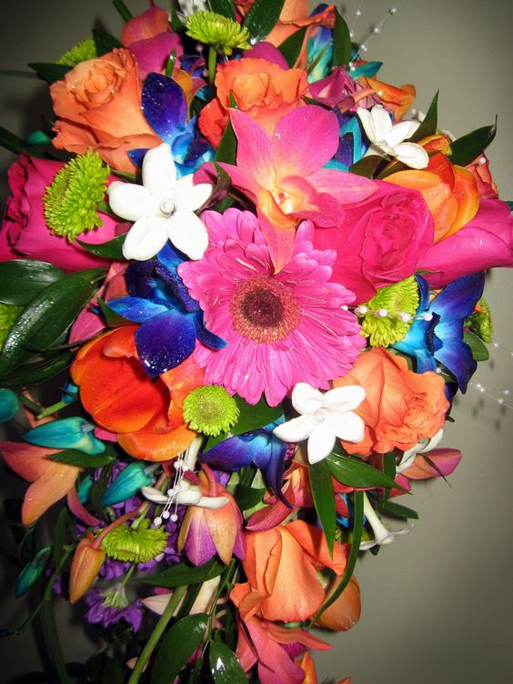Colorful cascade with Orchids, Gerbera Daisies, Tulips, Roses, and Stephanotis. Perfect for our destination wedding brides or a wedding with a tropical flair!