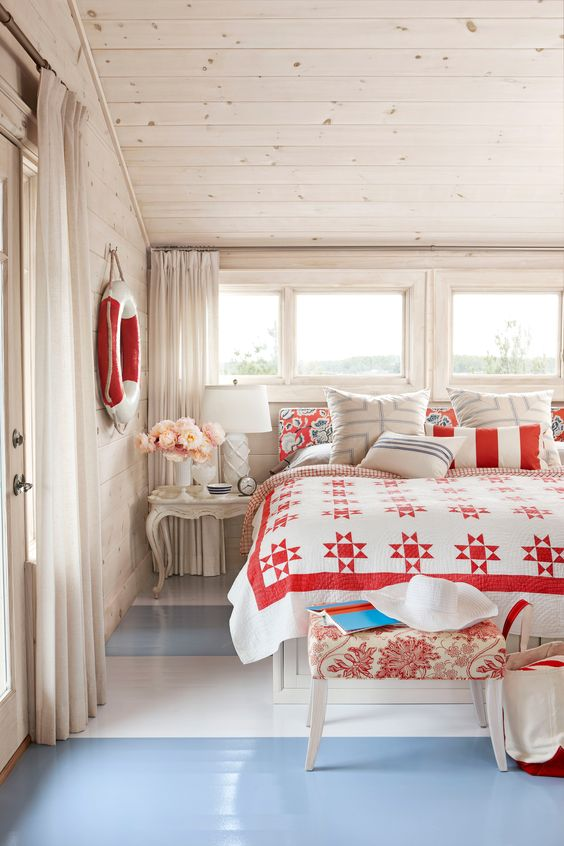 Whitewashed walls, blue stripes on floor, and red accents in a #cottagestyle bedroom by #SarahRichardson for a beach house