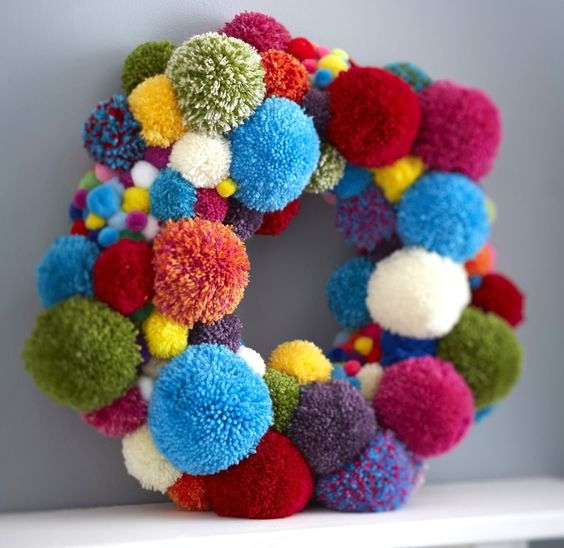 Learn how to make a pom pom wreath for Christmas with this great how to, perfect for both grown up bedroom doors as well as little ones! Let's get making! #pompom #worldpomination #pompomwreath