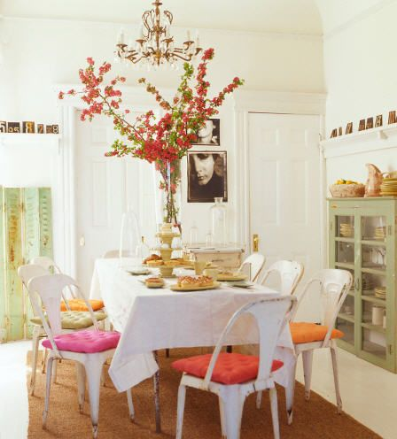 spring dining room. mismatched chair cushions, mainly white with dusty coloured accents.