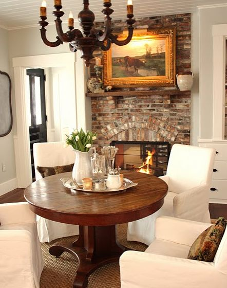 cozy dining french farmhouse round table upholstered chairs brick fireplace