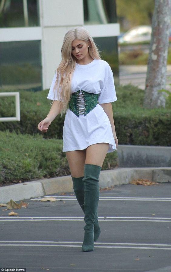 Kylie Jenner lleva una camisa blanca, unas botas de tacón verdes y unos aretes blancos. La camisa costo cincuenta dólares, las botas costaron trescientos dólares, y los aretes costaron cien dólares. Más