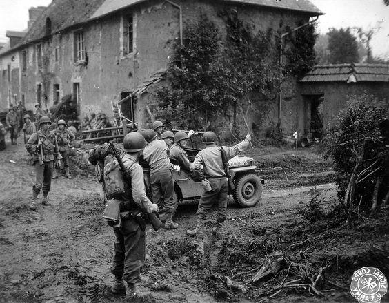 Le Major General Manton Sprague Eddy (à droite dans la jeep, la main sur le pare-brise), commandant de la 9th Inf. Div. US, demande des informations à un officier de l'infanterie le long d'un chemin de terre. En arrière plan des GI's se reposent près d'un corps de ferme. Photo prise le 26 juillet 1944 au hameau de La Courmiette, au sud-est des Champs-de-Losque (nord-ouest de Saint-Lô).