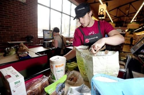 Cashier TC Jamison loads groceries into a customer's bag at Alfalfa's in Boulder last year. The Boulder City Council is considering banning or charging a free for the use of disposable paper and plastic bags. ( MARK LEFFINGWELL )