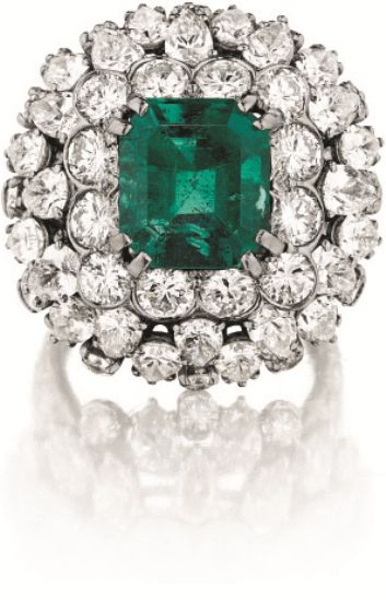 An Emerald and Diamond Ring - Set with a rectangular cut-cornered emerald, weighing approximately 4.43 carats, within a circular-cut diamond surround, further enhanced with a pear-shape and circular-cut diamond bombé gallery, to the pavé-set diamond half hoop, mounted in platinum. Signed 'DAVID WEBB'