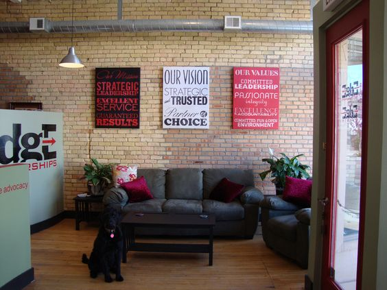 An ad agency dresses up their industrial modern office space with canvas gallery wraps of graphic art stating their company's mission, vision and values statements.