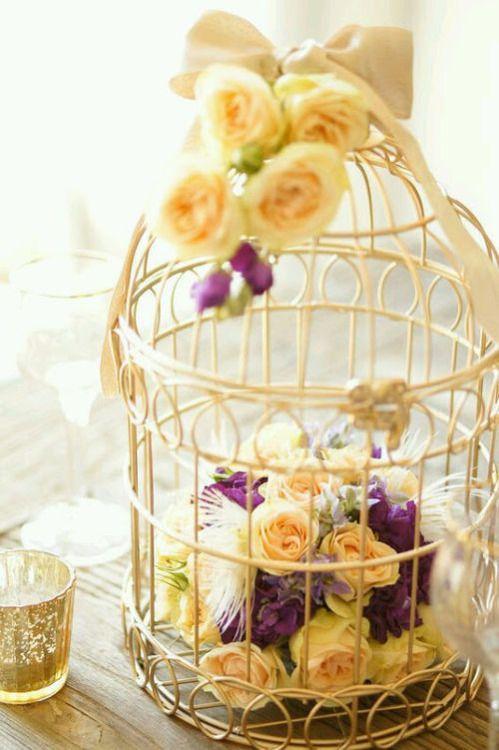 flower arrangement in a birdcage for a centrepiece