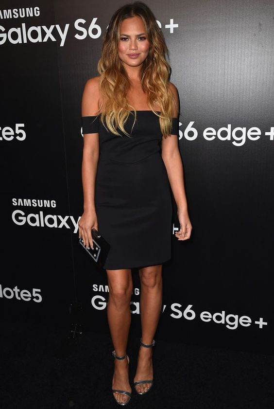 Chrissy Teigen com look todo preto em tapete vermelho.