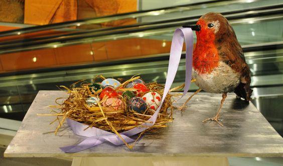 """""""A MISURA D'UOVO!"""" di  Giulia Chiarle, Elisa Zaino  classe  V° RC  Gli elementi della composizione sono un pettirosso in carta pesta, che tiene nel becco un nastro, con il quale avvolge un nido contenente uova dipinte.   Il tutto è posizionato su una tavola di legno cromata utilizzando una bomboletta spray.  Il tema della Pasqua è richiamato dagli elementi primaverili come l'uccellino e da uno dei simboli più ricorrenti della festività, ovvero le uova."""