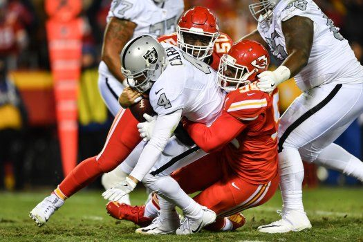 KANSAS CITY, MO - DECEMBER 8: Quarterback Derek Carr #4 of the Oakland Raiders is sacked by defensive tackle Rakeem Nunez-Roches #99 of the Kansas City Chiefs at Arrowhead Stadium during the first quarter of the game on December 8, 2016 in Kansas City, Missouri. (Photo by Peter Aiken/Getty Images)