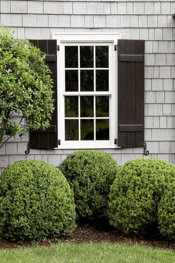 Board-and-batten shutters lend a more relaxed feel than louvered ones. Regardless of the style, shutters should be sized to be functional and finished with shutter dogs.     Classic cottage essentials: Cedar shutters, (NDB), shown custom painted, from $130/pair; finelinemillwork.com: