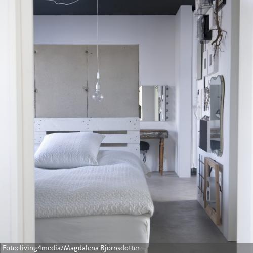 Das selbstgebaute Bett aus weiß angestrichenen Paletten mit einer Trennwand aus Spanplatten wirkt zusammen mit der Kabelleuchte sehr modern und zeigt kreativen Industrie-Chic. Die unfertige Rohbau-Optik verleiht dem Schlafzimmer mit der kreativen Wandgestaltung einen besonders kunstvollen Charme.