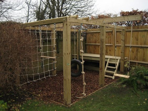 Children's playframe with play bark, swing, knotted rope, climbing net, swinging tyre, trapese and platform