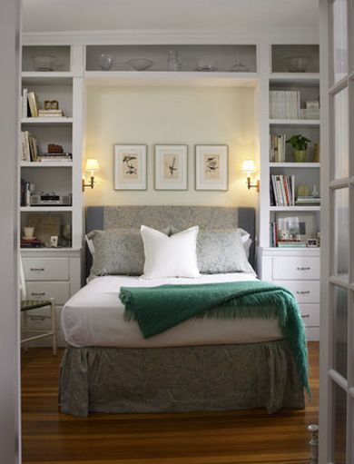 built-in shelves and cabinets framing the bed. Sconces.