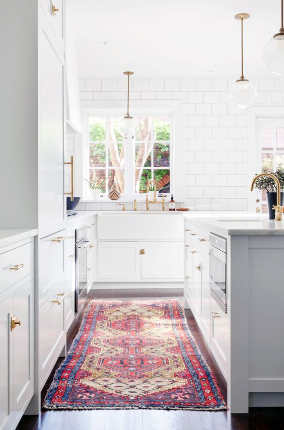 White kitchen: white subway tiles to ceiling with grey grout, marble benchtops, large farmhouse sink, brass traditional-style tapware, glass ball pendant lights with gold/brass rods, gold cabinet handles, white Shaker cabinets, long vintage rug, timber floorboards, island bench with undermount sink: