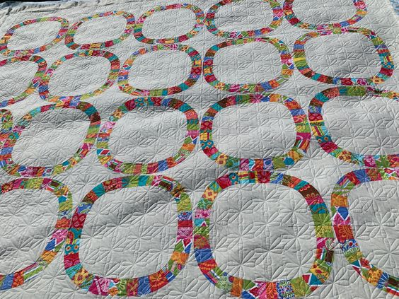 This quilt pattern is called Single Ladies. It's a twist on the double wedding ring. Isnt that funny? I think the daisy square quilt design mimics the square rings & the small size really stands out at the same tine emphasizes the pattern of the block.
