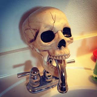 Cheap Halloween skull slipped over faucet is easy kitchen or bathroom decor