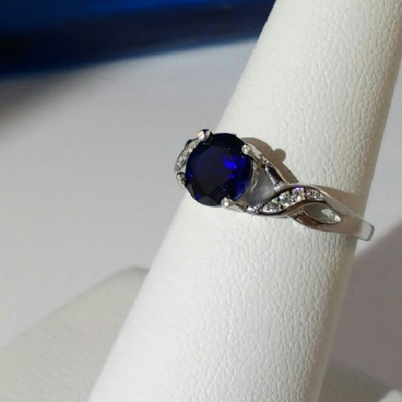 1.7 Carat Created Blue Sapphire Ring This is an exquisite engagement ring and an excellent choice for everyday enjoyment. The 7mm round cut , created blue sapphire gemstone exhibits excellent color and clarity. It is identical to a natural blue sapphire in every way. This size 8 platinum over sterling silver ring is accented with six 1mm round cut created white sapphires. See gemstone details in this listing. New. Jewelry Rings