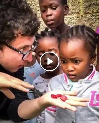um homem mostra truque para crianças africanas…