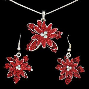 "Product # DMM23879 - This pretty poinsettia jewellery set will add a festive touch to your holiday ensemble! Bright red finish with European crystals in the centre. Necklace has 16"" chain with lobster clasp closure and 1""Diam. pendant. Fish hook style earrings are 1-1/2""L x 1""W. Ages 15+. Gift boxed."