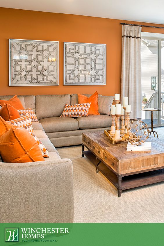 Orange walls, patterned artwork and light carpets add to the perceived space of the Barrington design's living room. A beige L-shaped couch and rustic wood coffee table make it the perfect entertaining space or gathering area. #DreamHome: