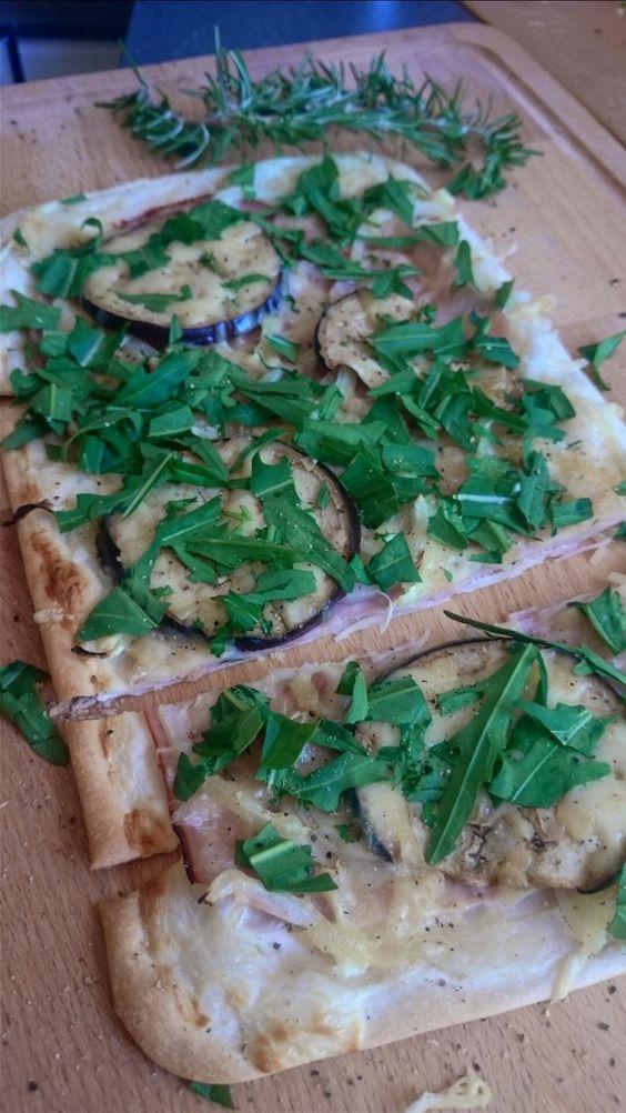 Schneller Flammkuchen - perfekt für heiße Sommertage  Flammkuchenteig mit Sauerrahm bestreichen und nach belieben belegen. Hier zB mit Schinken, Zwiebeln, Aubergine, Käse und frischem Rucola aus dem Garten
