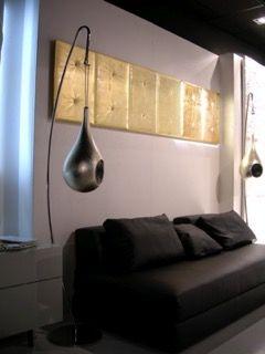 Parete con divano in pelle nera e decorazione a parete realizzata con tasselli in gesso decorate a capitonet e finite a foglia oro.