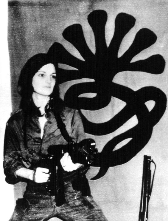 Patricia Hearst posed in front of the Symbionese Liberation Army emblem, April 1974.