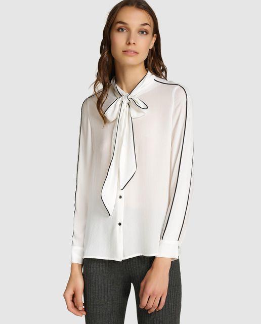 Blusa en color blanco, de manga larga y puños abotonados. Con cierre delantero de botones, lazada en el cuello y adorno de contrastes en negro.