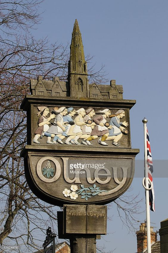 Carved wooden town sign at Olney Buckinghamshire England UK famous for the annual pancake race. The sign depicts the Parish Church and housewives participating in the pancake race