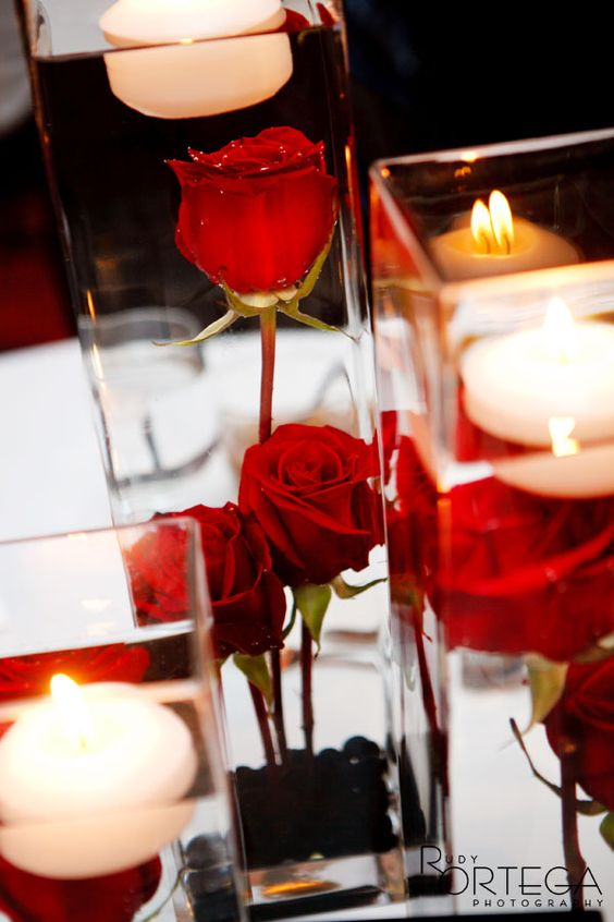Submerged red roses with a floating candle naakitifloral