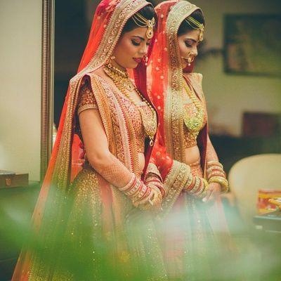 candid bride shot,b through the mirror shot, orange lehenga, gold border, rani haar, gold mathapatti, orange dupatta
