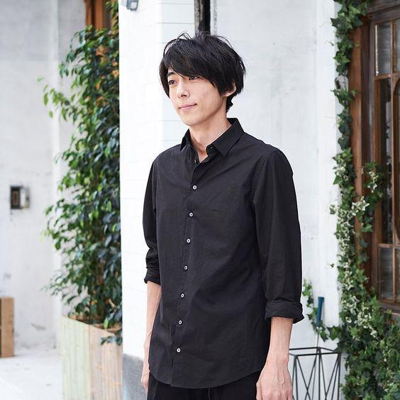 黒いシャツを着て庭に立っている高橋一生の画像