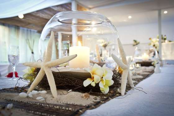 Wedding Bridal Table Beach Theme with candle and Frangipani Flowers - vkp-australia/Getty Images