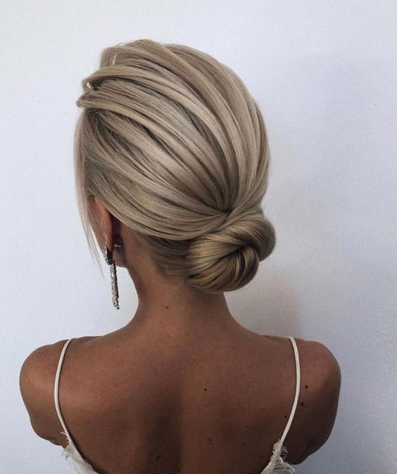 Sleek bridal low bun hairdo.