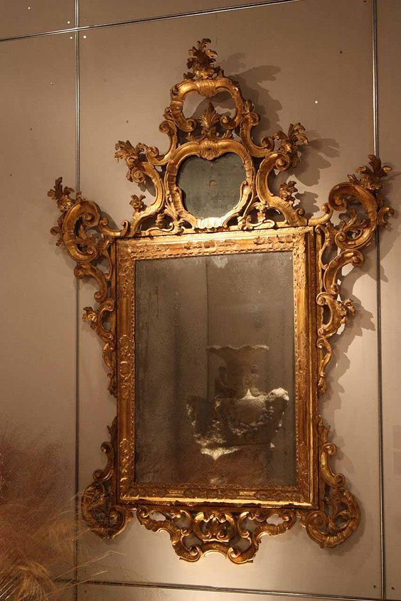 A 17th century French Baroque limestone fountain is reflected in the degraded mercury plate of an 18th century Venetian Baroque mirror.  Therien & Co.