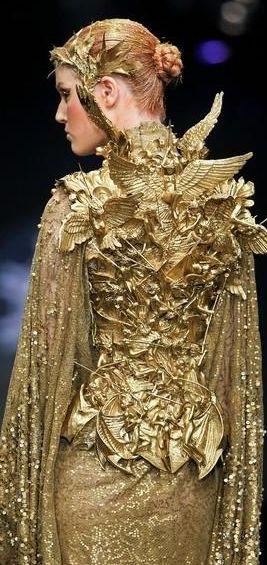 Alexander McQueen The goddess of war wears ever changing armour depicting scenes of war.