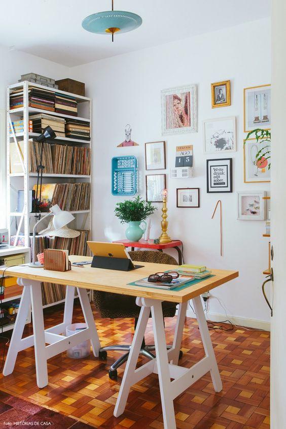 Escritório criativo da blogueira Chris Campos com mesa de cavalete e parede repleta de quadros e objetos.: