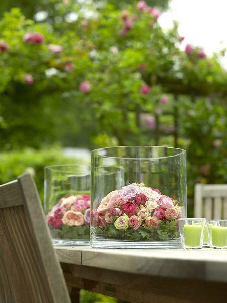 Grote tafel in de tuin, grote glazen vazen op de tafel, bloemen, eten, vrienden, wijn, perfect toch.