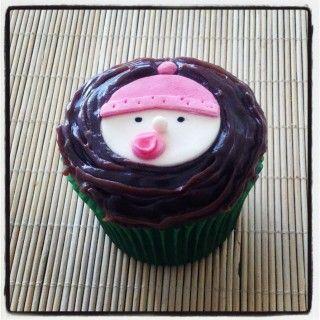 Cupcake Bebê com Gorro Rosa no Chocolate | Cupcake bebê com gorro rosa no chocolate, cobertura de chocolate e pasta americana. Sabor do recheio e da massa do bolo de sua preferência.