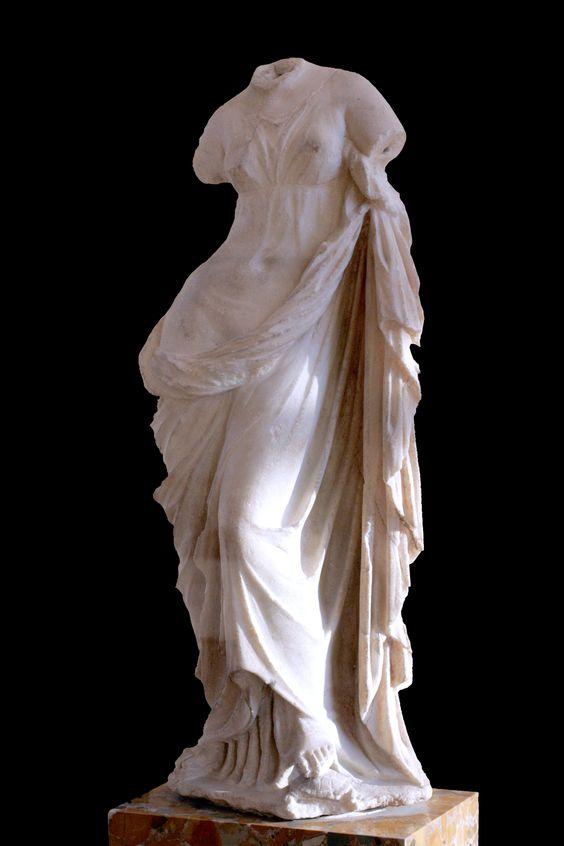 Afrodita Urania, drapeada más que desnuda, con sus pies descansando sobre una tortuga