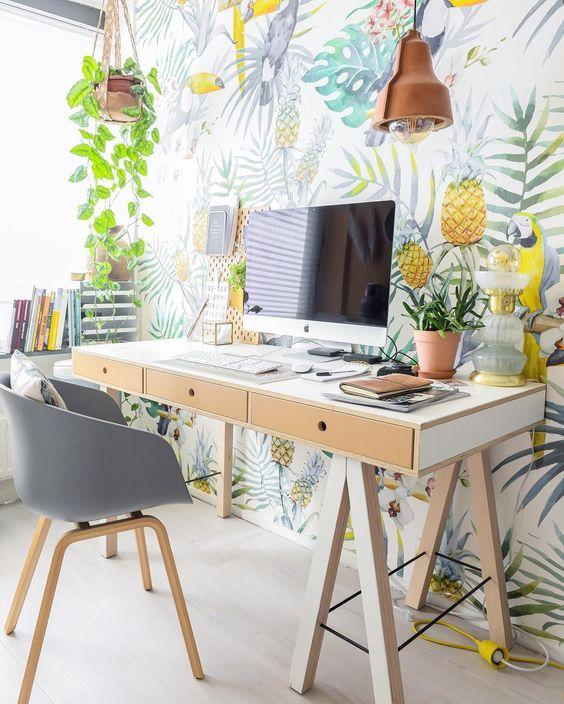 Vrolijk behang met bladeren en papagaaien tegen de muur achter bureau in tienerkamer