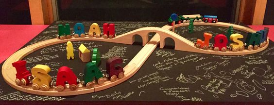 Becky works for a toy company that specializes in trains. Jon works for the forestry department.  We got them this wooden train track. We also played her brothers weddings. They have 3 sons Isaac, Joshua and Noah so we added these alphabet train cars. All their guests signed the board. #Wedding #WeddingGifts #SpecialGifts