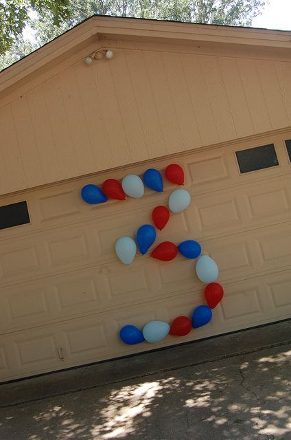 Tape balloons in the shape of the birthday age on the garage door on the day of party...(What a cute and easy idea to add to any birthday party!)