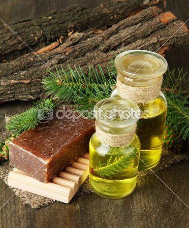 Sabão feito à mão e garrafas de óleo da árvore do abeto em fundo de madeira —…
