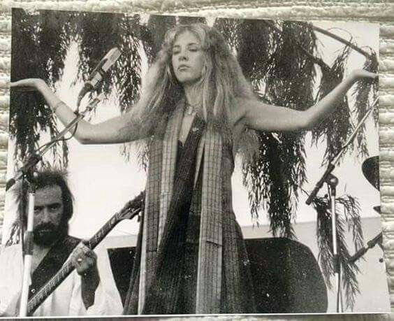 Stevie performing onstage outdoors ~ ☆♥❤♥☆ ~ in a strange pose and a weird facial expression with bassist John Mcvie behind her