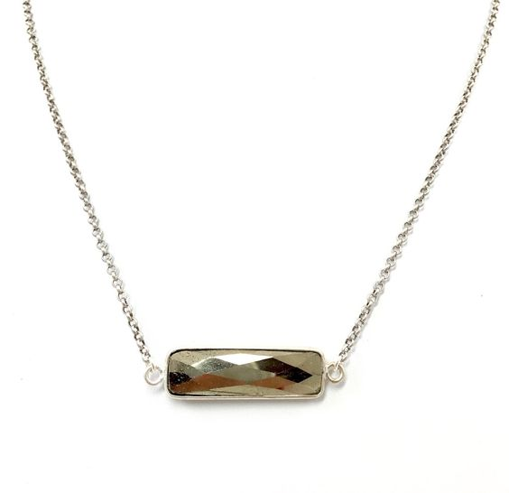 This faceted pyrite rectangle pendant with silver plated bezel hangs on a matte silver plated chain.