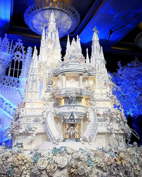This fairytale castle wedding cake features incredible sugar work detail, including a carousel of horses and hundreds of flowers