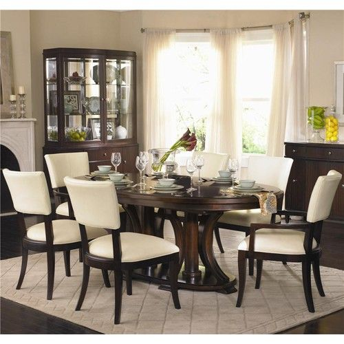 Defined Formal Oval Dining Table And Upholstered Cream Leather Chairs