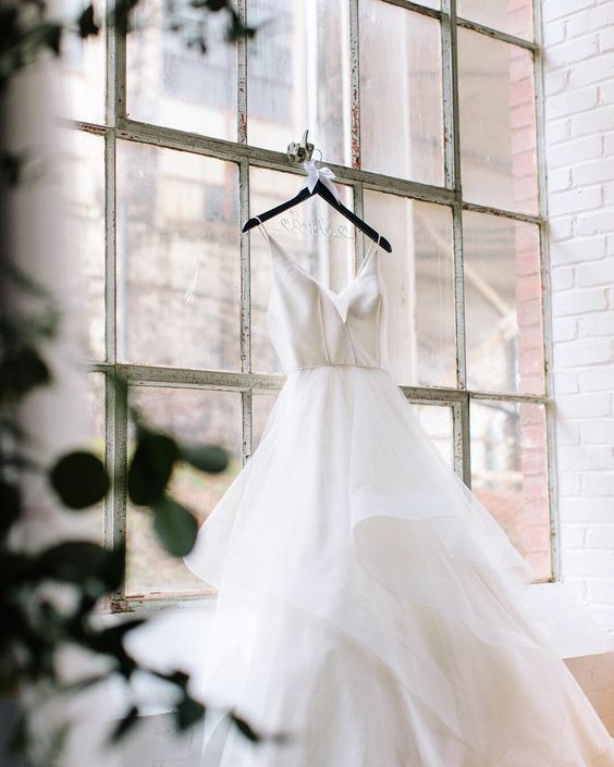 It's all about the wedding day details! This beautiful modern and romantic wedding dress looks so elegant and charming in this little window nook of the industrial venue the wedding took place at! An added touch of greenery makes It the perfect detail wedding picture ✨ #greenweddingshoes #weddingdresses #bridesmagazine  #romanticweddings #thatsdarling #jordynschirripaphotography